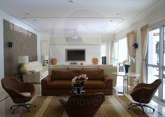 A sala para quatro ambientes conta ainda com um living room decorado por sofá em tecido suave ao toque e poltronas em fibra natural. Mesas de apoio para vasos de cristais, orquídeas e um tapete listrado completam o décor.