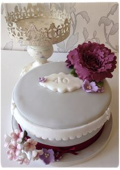 Vintage inspired ruby wedding anniversary cake, with large gumpaste peony, rose and a spray of white and purple pulled flowers