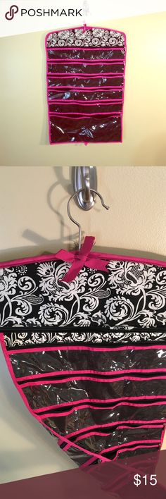 Hanging Jewelry and Accessory Holder Spacious, double sided, zipper closure jewelry and accessory holder. Great for traveling and saving space in bathroom or closet. Hanger is same size as clothing hanger. In great condition! Bags Cosmetic Bags & Cases