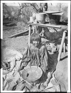 Photographic portrait of an Apache Indian woman basket maker, ca.1880. She is sitting on a cloth on the ground with a partially finished basket in her hands on her lap. An awl lays in the basket. Several sheaves of straw sit at her side. She is wearing a plaid dress over a dotted dress. Her hair is cropped above her shoulders and has bangs. Behind her is table on which which sit a few pails and a cup. The trunk of a tree and brush are visible in the background.