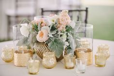 Soft, romantic centerpiece in a gold vintage vase with gold mercury glass votives.  Blush and peach garden roses with dusty miller to accent.  Designed by Bella Flora 30a.