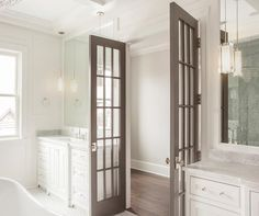 Gray French doors open to a master bathroom filled with separate washstands adorned with glass pulls topped with carrera marble under inset mirrors illuminated by glass column pendants.
