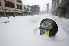 A parking meter pokes out of a snow bank during a blizzard, Saturday, Feb. 9, 2013 | Portland, Maine.