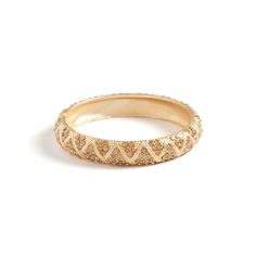 "Kristen Gold Bangle  The Kristen gold bangle is brimming with texture and shine. This easy on piece is a perfect choice for a little last minute glam. Kristen's triangular CZ pattern adds interest to this versatile bangle, perfect for stacking.  - Gold tone metal, CZ's - 1/2"" wide, 2 1/2"" diameter - Hinge closure"