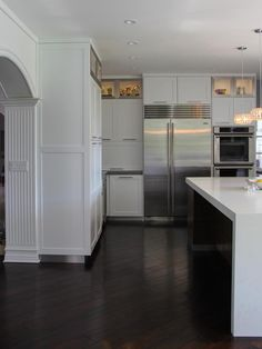 Stainless steel frames are used in upper display cabinets to tie in the stainless steel appliances in this contemporary kitchen.