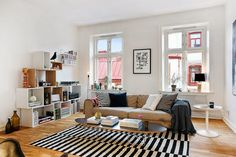 tan sofa in a Scandinavian apartment - layered with black and white pillows