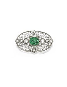 Platinum, Demantoid Garnet and Diamond Brooch, Circa 1910 The cushion-cut demantoid garnet weighing approximately 5.80 carats, within openwork surrounds set with numerous old European and single-cut diamonds weighing approximately 2.15 carats.