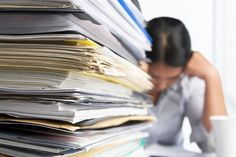 a large pile of paper next to a woman with her head down on the desk
