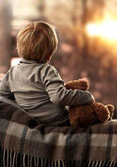 Jongetje met teddybeer kijkend naar de zon