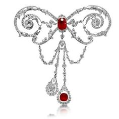 A Diamond, Ruby and Platinum Stomacher Brooch, by Joseph Chaumet, circa 1900  Designed as an undulating ribbon bow, centering a cushion-cut ruby of 7.00 carats in a diamond scroll openwork, and suspending two drop shaped elements set with an oval-cut diamond of circa 2.50 carats and a cushion-shaped ruby for 3.50 carats. Mounted in platinum with a total diamond weight of approximately 19.50 carats. French assay marks and maker's mark for Chaumet. The rubies are from Burma origin with no…