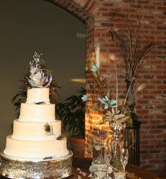 wedding cake table with jeweled initial monogram, pearls, crystals and peacock feathers accent