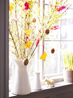 Branches adorned with hanging bunny and egg decorations, in a SOCKERÄRT vase, make a charming springtime display.