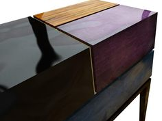 A gracious tribute to Mies van der Rohe, the Proportion II Nightstand is an eccentric and luxurious mix of black lacquer over silver leaf, radiant orchid lacquer over gold leaf, petrol blue lacquer and caviuna wood. The interior owes its softness to the satinwood. The base remains robust with solid wood lacquered in piano black.