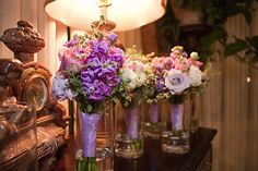 Lavender stock, ranunculus, and roses are adorned with swirling herbs for the bridesmaids' bouquets.