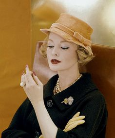 1959 Sara Thom in hat of pale orange feathers to look like silk by Adolfo of Emme, worn with tweed coat and a Verdura brooch
