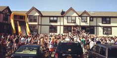 A photo of a party in front of a couple of residential buildings.