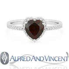 The featured ring is cast in 14k white gold and showcases a heart-shaped garnet center gem set in a 3-prong setting and accentuated by round cut diamond sidestones set around the center gem and on both sides of the band