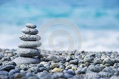 Stones pyramid on pebble beach symbolizing stability, zen, harmony, balance, concept with blur sea background