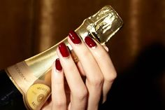 Feeling celebratory? Try a twist on the ever classic red nails, throw a champagne half moon in the mix