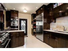 Dream kitchen! Dark wood, light floors and countertops, stainless-steel appliances, so much counter and cabinet space!