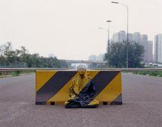 Fotografía del año 2007 que muestra al artista chino Liu Bolin, considerado el 'hombre invisible', sentado sobre una barrera en China.