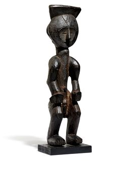 Resting on two feet, this figure is the representation of a clan ancestor. The very sculptural figure whose body is composed by a succession of inwards and backwards curves. The heart- shaped face is inscribed in a round face delimited by thinely carved engravings. In 100 Peoples of Zaire, Marc L. Felix mentioned a ritual practice to some Mbole figures giving this dark smoky patina. Remains of an old collection inscription in white ink on the foot.
