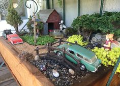 Miniature Fairy Garden, HIDE & SEEK is nestled in Fairy Pines. The boy fairies are playing a game of Hide & Seek. The scene includes vintage cars. The barn has a red Porsche inside of it, and a '57 Chevy is being towed. A Nomad station wagon is coming over the bridge. There are two owls: one is above the barn; and the other one is on the street post and is fixated on the ducks in the creek. Look carefully and you will see squirrels and raccoons. 7/2015