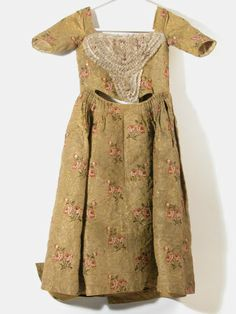 Girl's dress (aged 6 years), 1750-1770. Mustard yellow silk brocade with striped gilt weft, applied stomacher of lace (blonde) and paper rosebuds.