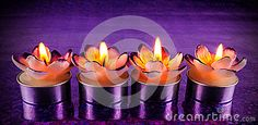 Flower shaped candles lighted on purple surface.