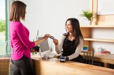 Good looking brunette paying with credit card stock photo