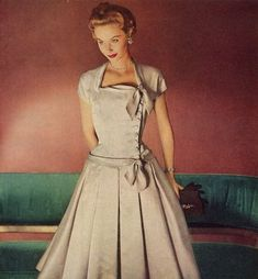 Model wearing a cocktail dress in neutral tones. Nifty-fifties: