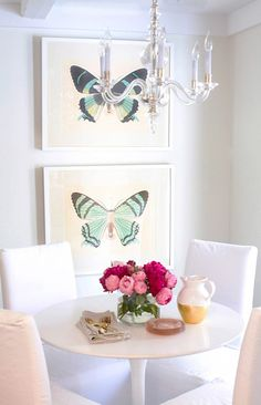 Abby Larson of Style Me Pretty's feminine dining area with pretty butterfly prints, a chic chandelier, and stylish round table