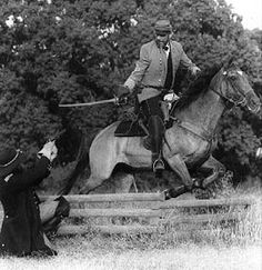 Mounted Combat: The Rider Rider focuses his attention on his opponent as the horse jumps the fence.