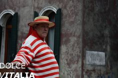 Funny Gondolier standing on a bridge and catching tourists to his Gondola…