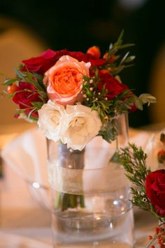 This table features a bridesmaids bouquet that consists of white spray roses, a coral garden roses, red roses, and eucalyptus. The vase is decorated with a sheer gold ribbon. The table also includes a small glass vase filled with a red rose, wax flower, and red berries. Mercury glass is also incorporated on the table.