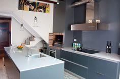 Encimera blanca elegante y funcional que combina con los toques rústicos de esta cocina.