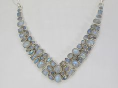 Andrea Jaye Collection Moonstone Mosaic Necklace  An intricate mosaic of petite cabachon Sri Lankan Rainbow Moonstones form a lovely iridescent necklace. Several large oval shaped stones anchor a variety of gemstone shapes and sizes, all set in 925 sterling silver.