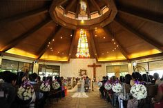 The couple tied the knot at Chapel on the Hill in Batulao, Batangas. Iron stands held pomanders of white roses with violet ribbons. | www.BridalBook.ph