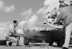 Stirling Moss at 1958 Nassau Speedweek. In 1958 Stirling Moss was the world's top-ranked road racing driver. In this photo he pitches in to change a tire during the Nassau Speedweek Trophy Races. In the Aston-Martin is George Constantine. Moss declined to drive in the '58 race because of the lack of prize money, although he won previously. Photo courtesy of Randy Cook and Motorspeed.