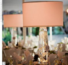 Lampshade topped with glass vase filled with water and strands of crystals