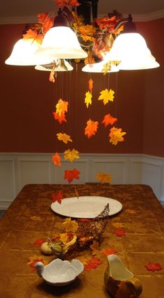Using fishing line and a bag of leaves from from the dollar store I created a fall scene for my Thanksgiving table! Hung from the light with colored paper clips to blend in! Spread out excess leaves on the table