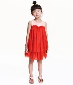 Rot/Rosa. Ärmelloses Kleid aus Webstoff und Tüll. Das Kleid hat in der Taille eine Teilungsnaht und im Nacken einen geknöpften Schlitz. Mehrlagiger,