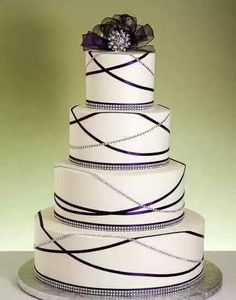 Lovely four layered round cake trimmed with rhinestones and purple ribbons.