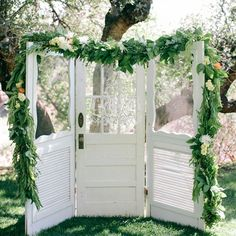 Shabby-Chic Wedding Arch ~ Three reclaimed vintage doors lavishly decorated with an elegant floral swag and chandelier served as the backdrop for the ceremony...
