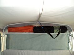 """Camper Bunk End Shelf: Rubbermaid shelving, Rubbermaid Bracket & Strap. """"cut the little drywall flanges off flush and then used small machine head screws to fasten them to the upright support poles in each bunk end. You could probably make it even easier to mount by just using self tapping machine screws. Then you wouldn't have to deal with pre-drilling a hole and such. The brackets are mounted on the inside part of each pole and lay flat against the mattress when I fold everything up."""""""