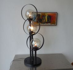I could live with this vintage mid century era tall table lamp... Love the 3 staggered height clear globes in hoops...