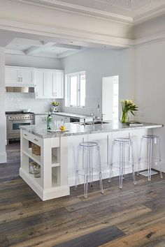 Backless acrylic stools sit in front of a white kitchen peninsula accented with slated shelves and a Super White Dolomite countertop completed with a stainless steel dual sink and a polished nickel gooseneck faucet fixed facing l-shaped Super White Dolomite countertops completed white shaker cabinets located under a window.