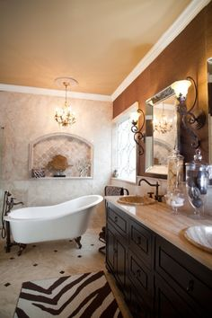 Master bathroom with a clawfoot soaking tub, and a zebra-striped rug to add some interest to the beige tile floor