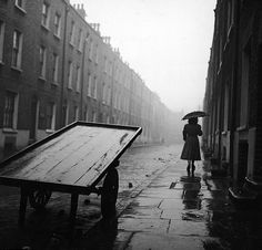 A woman walks down a rainy street in post-war Whitechapel, 1952