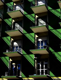 Green building with many identical balconies